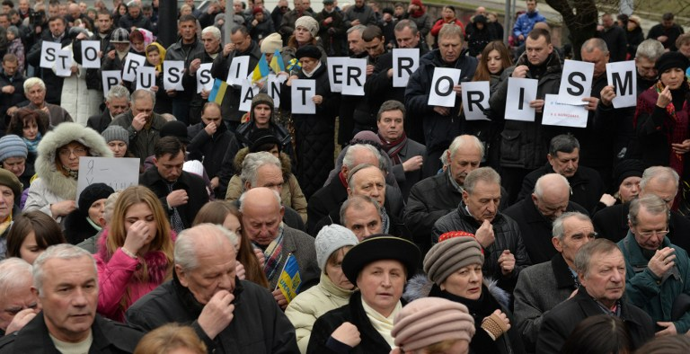 "People hold placard reading ""STOP RUSSIAN TERRORISM"" during a march in western Ukrainian city of Lviv on January 18, 2015, to pay tribute to the 13 passengers of a bus killed after a shelling by pro-Russian separatists in small eastern Ukrainian city of Volnovakha. Demonstrators ask Russia's President Vladimir Putin to stop war in Ukraine and supporting the terrorism. AFP PHOTO/ YURKO DYACHYSHYN"